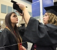 Kailey Tull, kinesiology, puts on Alexis Morton's, accounting, cap while waiting in the MPEC before Commencement Ceremony held in the Kay Yeager Coliseum, Dec. 12, where 440 crossed the stage. Photo by Rachel Johnson