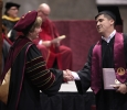 Suzanne Shipley, university president, congratulates Francisco Espinoza, applied arts and sciences, as he walks across the stage at the Commencement Ceremony in Kay Yeager Coliseum Dec. 12, 2015