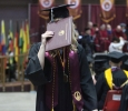 Haley Reid, special education, hides her face from the cameras as she walks back to her chair at Midwestern State University graduation, May 16, 2015 at the Kay Yeager Coliseum. Photo by Rachel Johnson