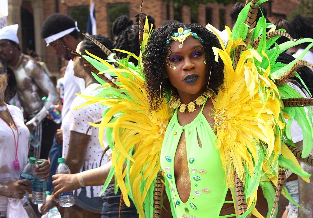 Edeesha Darwton, nursing senior, looks around at all the people dancing during the Caribfest Parade that looped from Dillard to Jesse Rogers Promenade Sept. 30. Photo by Rachel Johnson