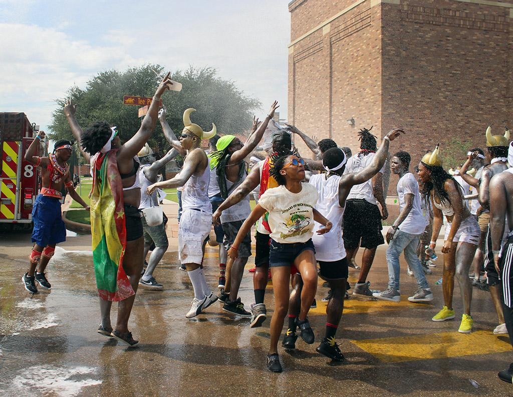 The Wichita Falls Fire Department sprays the participants in the Caribfest Parade while they dance, sung, and ran through it at the end of the parade infront of the Mass Communication building before they headed onto Jesse Rogers Promenade Sept. 30. Photo by Rachel Johnson