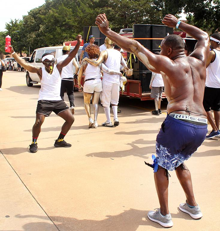 Dave Hughes, accounting senior, and Akeem Shaw, accoutning senior, start to dance together during the Caribfest Parade that looped from Dillard to Jesse Rogers Promenade Sept. 30. Photo by Rachel Johnson