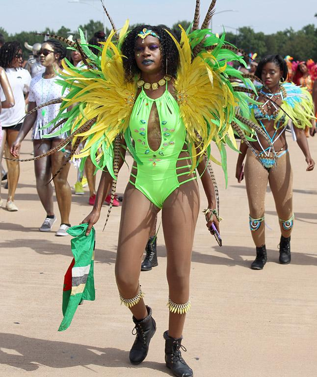 Edeesha Darwton, nursing senior, shoes off her brightly feathered green and yellow outfit at the 2017 Caribfest parade held in the Dillard parking lot Sept 30. Photo by Marissa Daley
