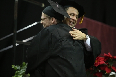 Fine Arts Dean Martin Camacho hugs Tyler Lasseter at graduation, Dec. 16, 2017. Lasseter received a Bachelor of Music degree. Photo by Bradley Wilson