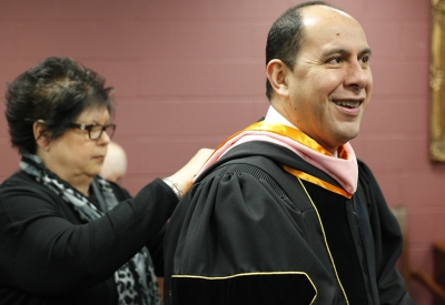 Treva Clifton, president assistant, helps Martin Camacho, dean of fain college of fine arts, with his sashes before MSU's commencement ceremony at Kay Yeager Coliseum. Saturday Dec. 16, 2017. Photo by Francisco Martinez