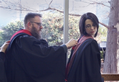 Eric Koger, associate profesor of theater, fixes the scarf on Christie Maturo, assistant proffesor of theater, at the fall 2017 commencement at the Kay Yeager Colliseum on Sat. Dec. 16, 2017. Photo by Justin Marquart