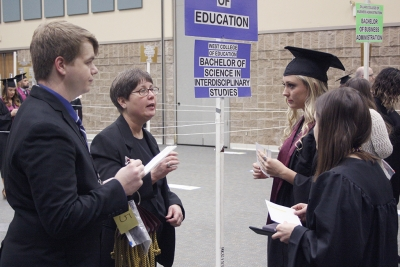 Henry Steele, mechanical engineering sophomore and student worker, and Bricelle Satterfield, assistant to the registrar, give information to Mackenzie Pierce, BS in Interdiscplinary Studies, and Aaron Campbell, BFA graduate, at the fall 2017 commencement at the Kay Yeager Colliseum on Sat. Dec. 16, 2017. Photo by Justin Marquart