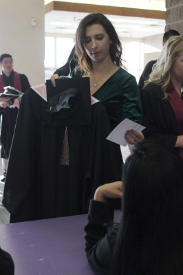 Aubrey Kass, bachelor of business administration, gets her card to fill out when she first arrives to the Multi-Purpose Entertainment Center to get ready for Commencement in Kay Yeager Coliseum, Sat. Dec. 16, 2017. Photo by Rachel Johnson