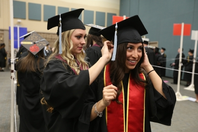 Mackenzie Pierce and Monica Melara, both candidates for a Bachelor of Science in Interdisciplineary Studies, get ready for graduation, Dec. 16, 2017. Photo by Bradley Wilson
