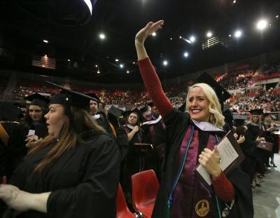 Linda Ross waves to her family and friends at graduation, Dec. 16, 2017. Photo by Bradley Wilson
