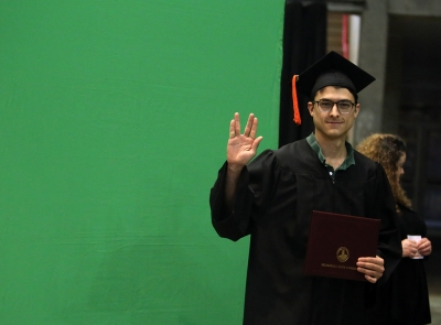 Michael Olaya pauses for a photo after graduation, Dec. 16, 2017. Photo by Bradley Wilson