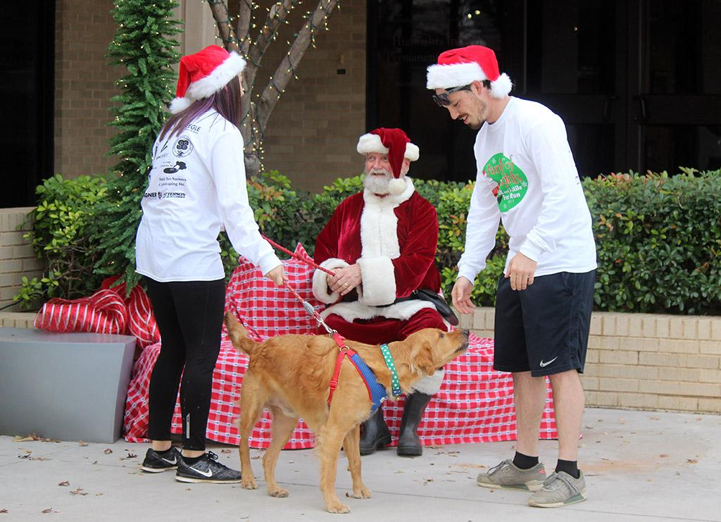 Caitlyn Cremeens, 2015 graduate, and Braden Wood, 2013 graduate, try to get a picture with their dog, Mack with Santa who was played by Wichita Falls COunty Judge Woodrow Gossom Jr. Photo by Rachel Johnson