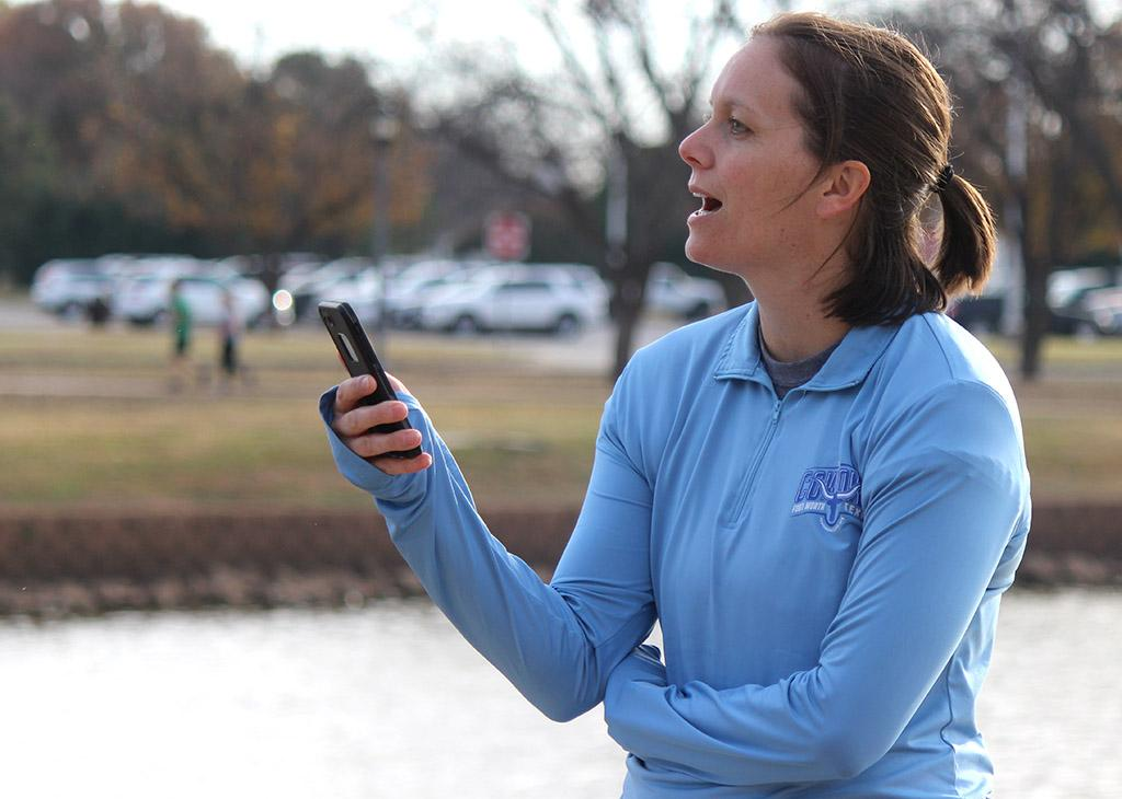 Angie Reay, directory of the Wellness Center, yells out words of encouragement and updates on time as the runners of the annual Fantasy of Lights 5k and 1 mile event loop around Sikes Lake, Dec. 2, 2017. Photo by Rachel Johnson