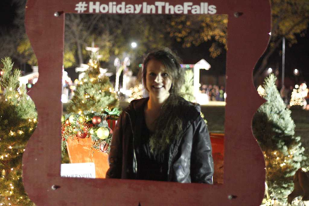 Michelle Chavez, music secretary, poses at the Holiday in the Falls picture frame at the MSU Burns Fantasy of Lights on the front lawn of the Hardin Building on Monday, Nov. 20, 2017. Photo by Justin Marquart