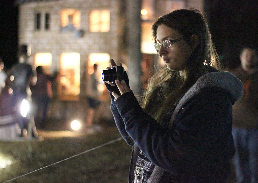 """Carina Peterson, radiology sophomore, takes pictures of the different lights and scenes set up at the opening ceremony of MSU-Burns Fantasy of Lights Monday, Nov. 20, 2017. """"I was walking around [campus] earlier and I thought it would be really nice to see this and I'm also here to see the Wind Ensemble,"""" Peterson said. Photo by Rachel Johnson"""