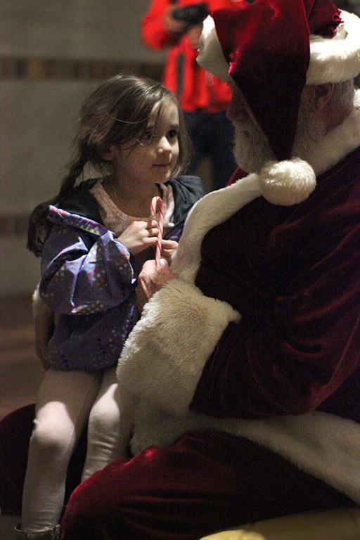 """Adilai McCurley, attendee, sits on Santa Claus' lap who was played by Woodrow Gossom Jr., Wichita Falls County Judge, who was playing Santa, during the MSU-Burns Fantasy of Lights Opening Ceremony. """"[Adilai] is from Lake Dallas, and they were so excited to be here. This was our first time going and we will definitely have to come back again,"""" Kristi Whyrick, Adilai's grandmother, said. Photo by Rachel Johnson"""