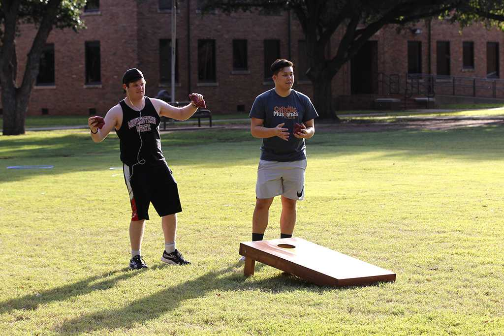 Steven Ehlert, criminal justice junior, Johnny Dang, pre med sophomore, both anticipate and egg on their opponents in a game of cornhole at the quad on Oct 18, 2017. Photo by Sara Keeling