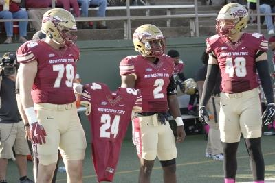 Kevin Fisher Jr., business managment junior, Sir'vell Ford, criminal justice junior, and Alec Divalerio, exercise physiology junior, carry the jersey of Robert Grays onto the field for the coin flip at the begining of the homecoming game where the Mustangs won 45-3 at Memorial stadium on Saturday, Oct. 21, 2017. Photo by Justin Marquart