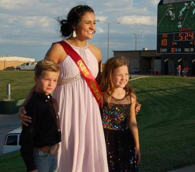 Miranda Rodriguez, education senior, poses with the two kids that escorted her onto Memorial Stadium for the announcement of Homecoming King and Queen on Oct. 17, 2017. Photo by Shea James