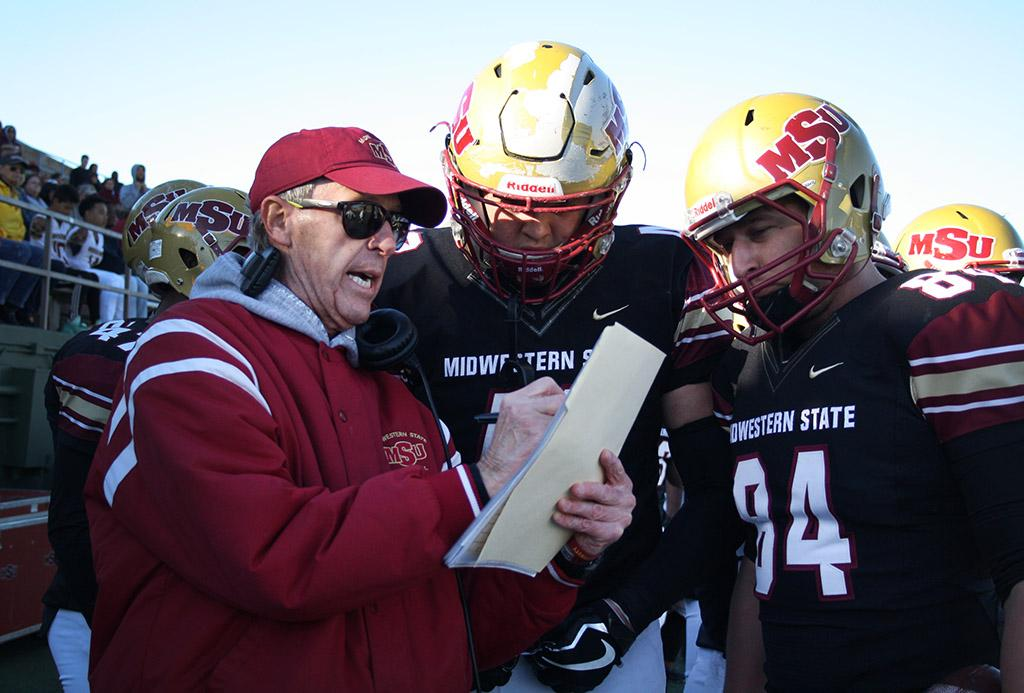 Head Football Coach Bill Maskill discusses plays with players Alec Divalerio, exercise physiology junior, and Mitchell Henton, mechanical engineering senior, during the last 5 minutes of the fourth quarter during the Round One NCAA II Playoff game against University of Sioux Falls at Memorial Stadium, Saturday Nov. 18, 2017. Photo by Rachel Johnson