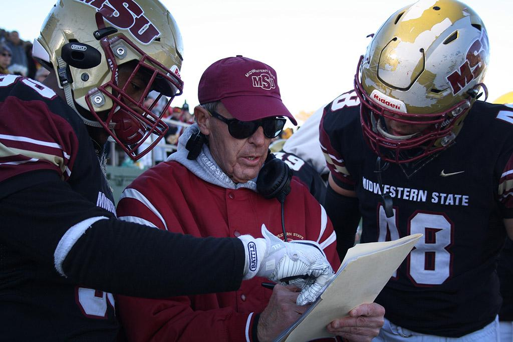 Head Football Coach Bill Maskill discusses plays with players Travon Ransom, criminal justice sophomore, and Alec Divalerio, exercise physiology junior, during the last 5 minutes of the fourth quarter during the Round One NCAA II Playoff game against University of Sioux Falls at Memorial Stadium, Saturday Nov. 18, 2017. Photo by Rachel Johnson