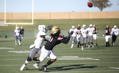 Wide receiver and mass communications freshman Daniel Petty attempts to catch a pass by quarterback and accounting junior Layton Rabb in the first round of the NCAA Division II playoffs against University of Sioux Falls. Nov 18. Photo by Bridget Reilly