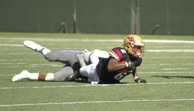 Wide receiver Brandon Sampson, applied arts and science senior, gets tackled with the ball during the NCAA II playoffs first round football game against sioux falls at Memorial Stadium on Sat. Nov. 18, 2017. Photo by Justin Marquart