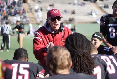 Head Football Coach Bill Maskill gives the team a pep talk during the second half of the NCAA II Round One Playoffs game during a time out called at Memorial Stadium. Photo by Rachel Johnson