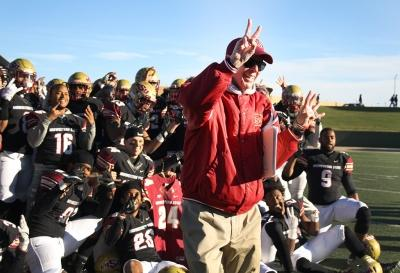 Head Football Coach Bill Maskill holds up the number 24 in honor of the recently deceased player Robert Grays, for a group photo after MSU beat University of Sioux Falls 24-20 in Round One NCAA II Playoffs game at Memorial Stadium. Photo by Rachel Johnson