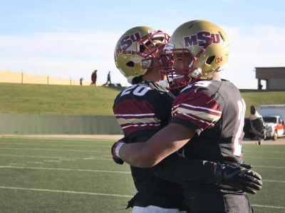 Jakari Domino, music freshman, and Kevin Hayes, undecided sophomore, hug after shaking hands with the University of Sioux Falls players after beating them 24-20, advancing MSU to Round Two of the NCAA II Playoffs against Minnesota State. Photo by Rachel Johson