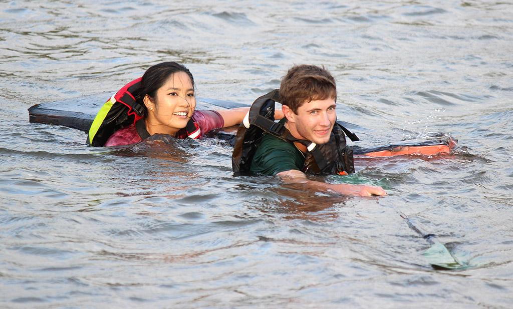 Kale Hutchins, general business freshman, and Andrea Mirasol, undecided freshman, swim their way back to shore with their sunken boat after only getting about 20 feet out before their ship collapsed on them during the Homecoming Boat Race 2017. Photo by Rachel Johnson