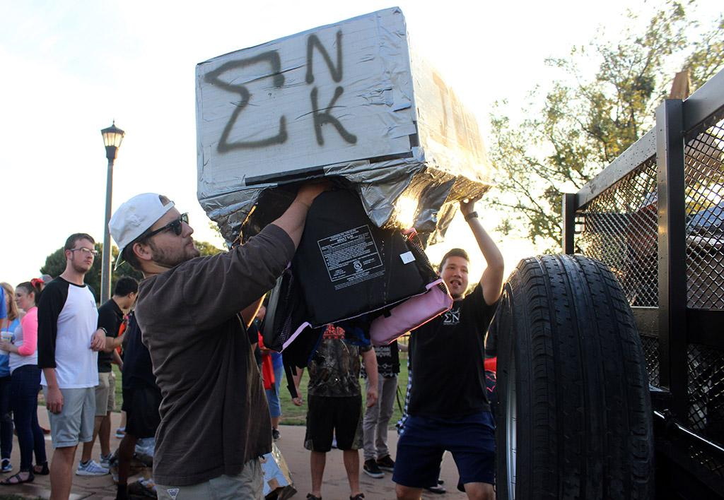 William Gibson, mechincal engineer junior, helps toss the Sigma Nu and Sigma Kappa cardboard boat at the end of the Homecoming Cardboard Boat race, Friday Oct. 20, 2017. Photo by Rachel Johnson