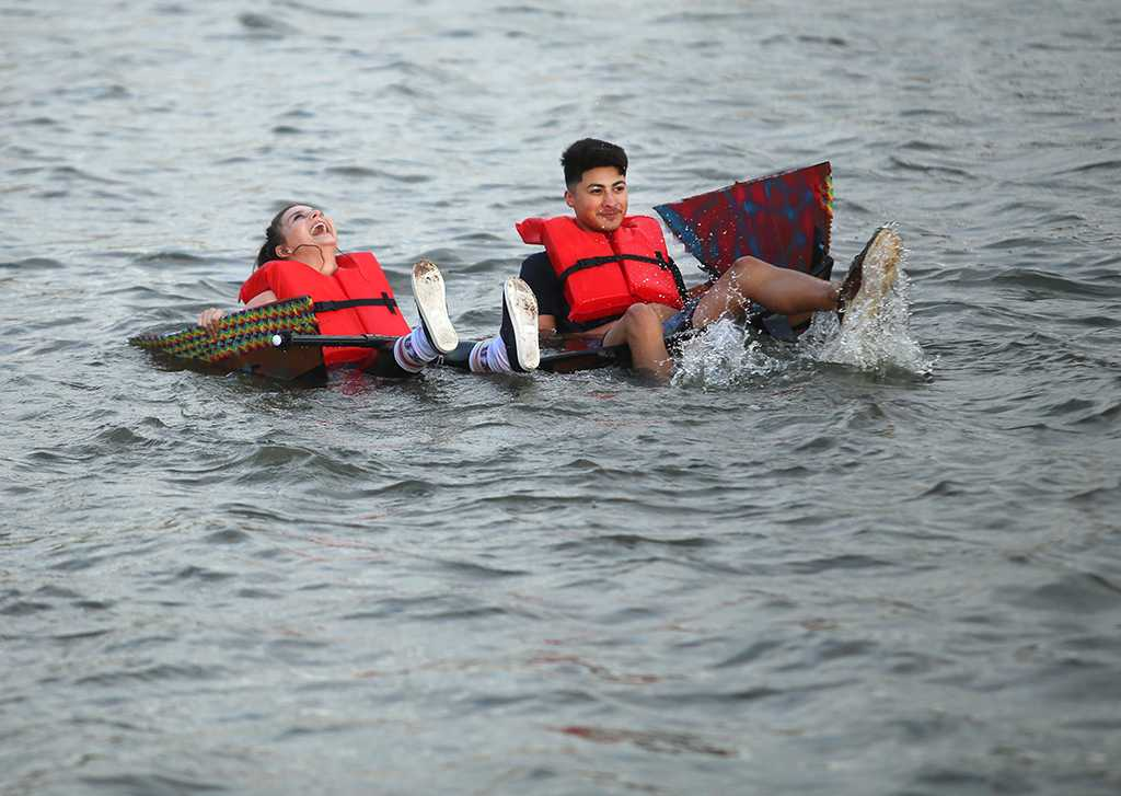 Mia Heck, mass communication sophomore, and Javier Suarez, mass communication sophomore, try to cross Sikes Like in their boat for Chi Omega and Sigma Alpha Epsilon. Their boat failed about 50 feet from the starting line. Photo by Bradley Wilson