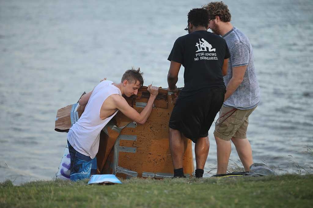 Luke Sanders, psychology senior, and Aaron Devaul, psychology senior, pull their boat from the water after  the homecoming cardboard boat race on Sikes Lake Oct. 20, 2017. Photo by Bradley Wilson
