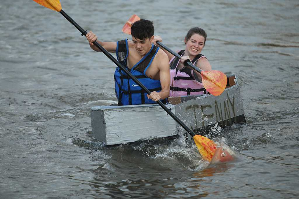 Racing for Sigma Nu and Sigma Kappa, Braxton Urioste, nursing freshman, Reece Crosby, sociology freshman, at the homecoming cardboard boat race on Sikes Lake Oct. 20, 2017. Photo by Bradley Wilson