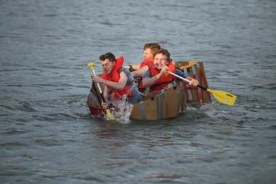 Casey Albrikes, radiology freshman, Zander Leary, math freshman, and Josh Gribble, biology sophomore, paddle the Residence Hall Association boat at the homecoming cardboard boat race on Sikes Lake Oct. 20, 2017. Photo by Bradley Wilson