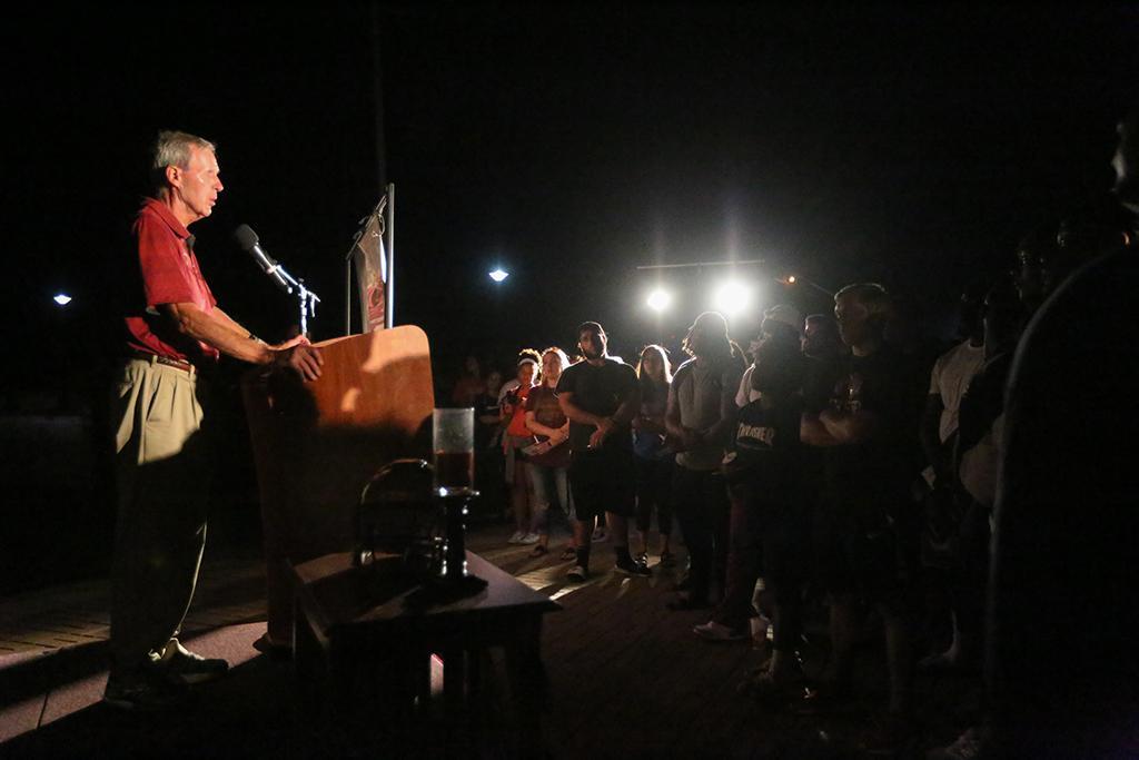 Bill Maskill, head football coach, speaks at the candlelight vigil remembering Robert Greys on Jesse Rogers Promenade on Sept. 21. Photo by Elias Maki