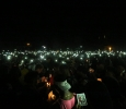 Students hold up flashlights at the candlelight vigil remembering Robert Greys on Jesse Rogers Promenade on Sept. 21. Photo by Elias Maki