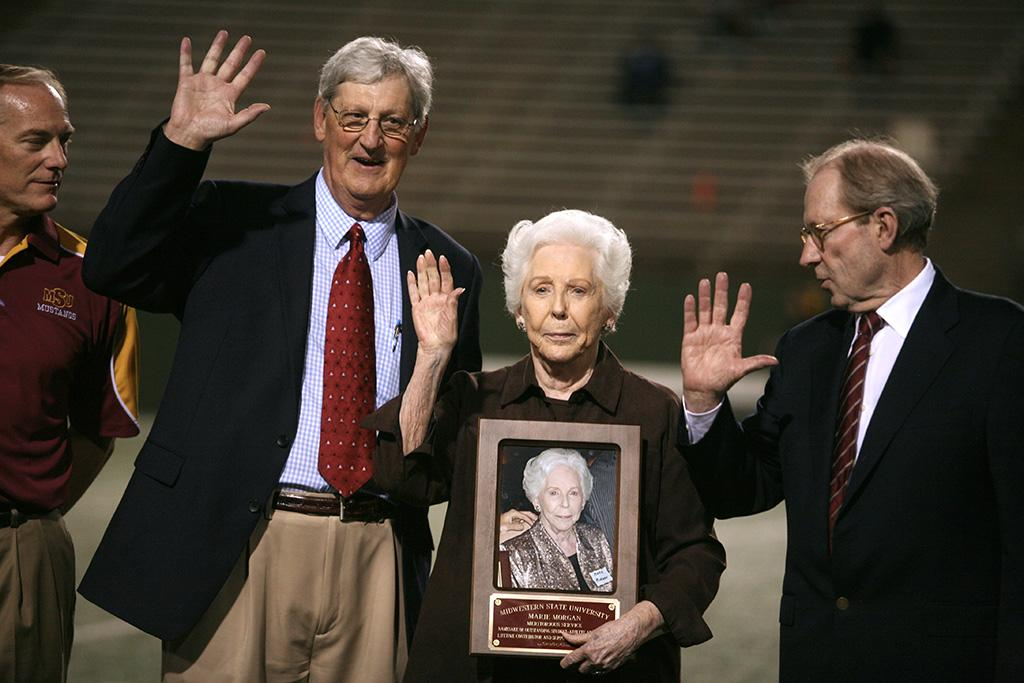 Athletic Director Charlie Carr and now-retired University President Jesse Rogers recognized Marie Morgan for Meritorius Service as the namesake of the outstanding student athlete and a lifetime contributor of the MWSU athletic program at the homecoming game, Oct. 25, 2015. Photo by Bradley Wilson