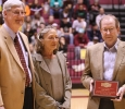 Jenee Gholson stands with now-retired University President Jesse Rogers and athletic director Charlie Carr at half-court during the ceremony that honored her husband Nick Gholson, Time Record News sports reporter, during the game against Eastern New Mexico University Jan. 11 in D.L. Ligon Colisuem.