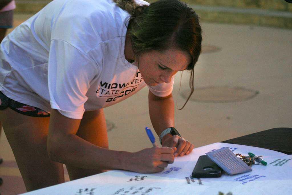 Nicole Coetzer, nursing senior, signs a poster for football player Robert Grays. Photo by Harlie David