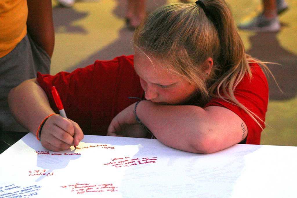 Molly Whitaker, special education sophomore, signs a poster for football player Robert Grays. Photo by Harlie David