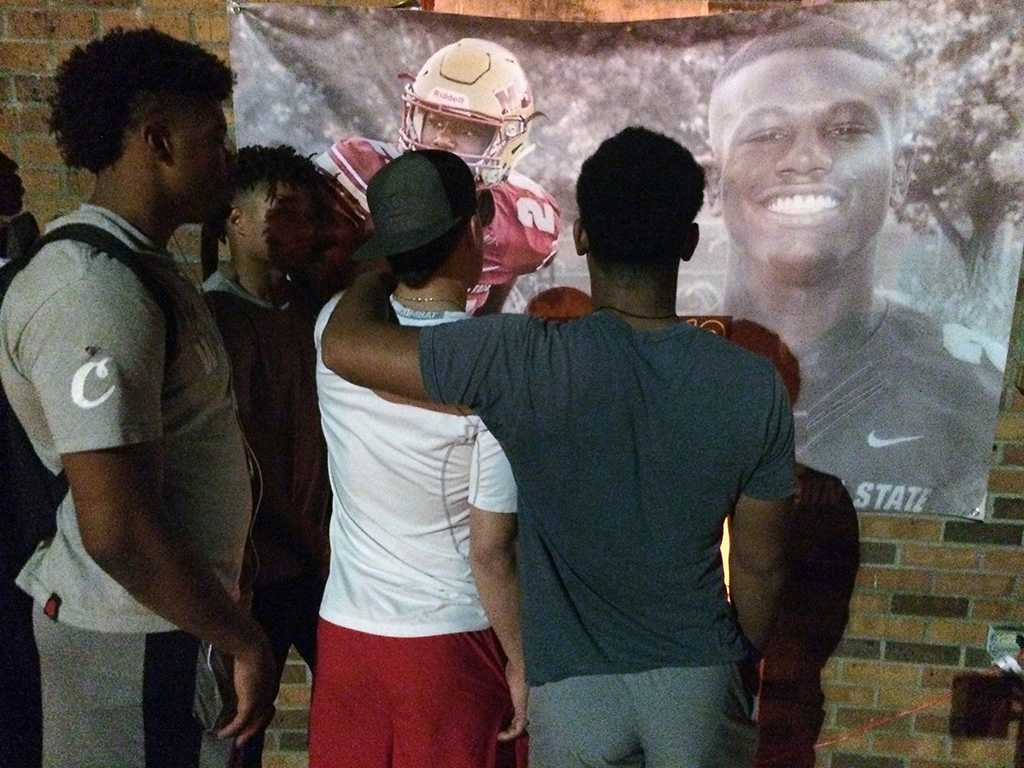 Football players honor injured player at the community gathering. Photo by Bradley Wilson