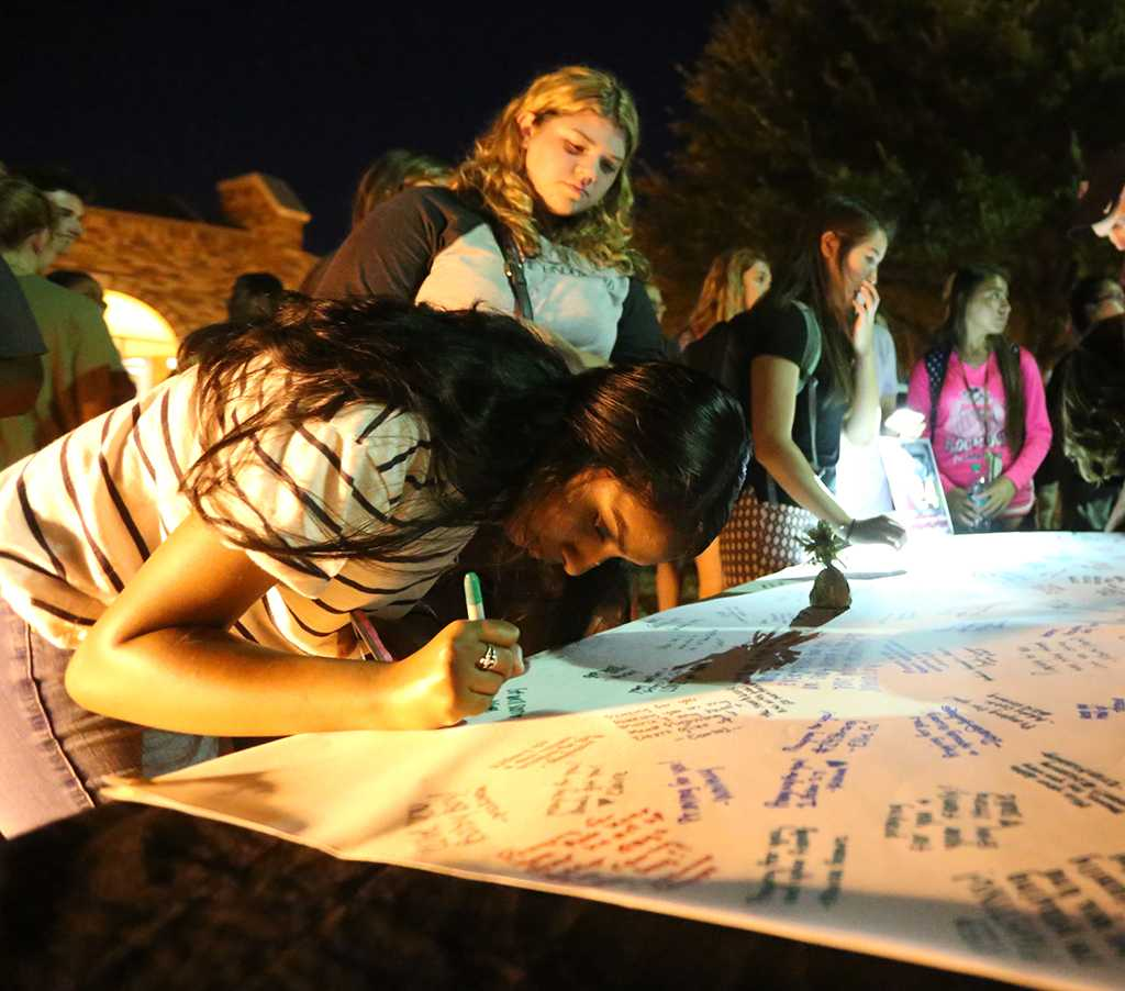 Juliana Matthew, exercise physiology sophomore, signs the poster at the community gathering. Photo by Elias Maki