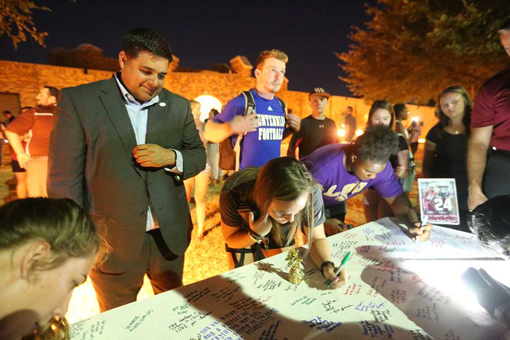 Taylor Robinson, exercise physiology junior, signs the poster. Photo by Elias Maki.