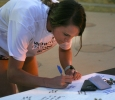 Nicole Coetzer, nursing senior, signs a poster for football player Robert Grays. Photo by Harlie David