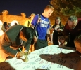 Wichita Falls Mayor Stephen Santellana, Jacob Sherrill, a respiratory therapy, and Provost James Johnston sign the poster for injured football player.