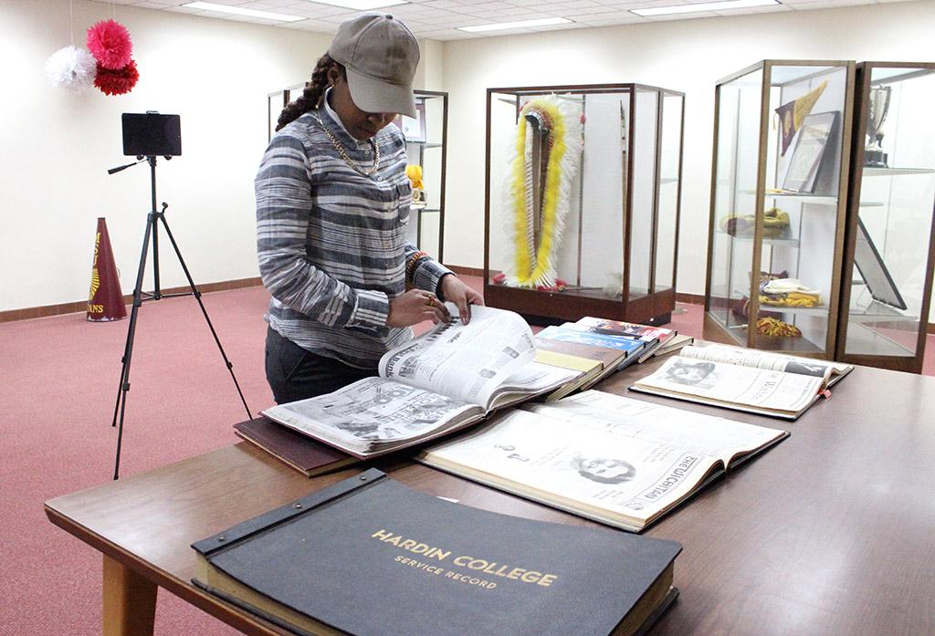 Rolanda Ferdinand, general business senior, looks through the old Wai-Kun and Wichitan editions that were scanned onto the MSU HIstory Display, which is on the second floor of the Moffett Library, and was unveiled Feb. 9. Photo by Rachel Johnson