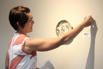 Empty Bowls Juror Kelly O'Briant announces the third place winner, a piece titled 'Altered Plate V' by artist Gratia Brown, at the Empty Bowls Gallery Reception in the Wichita Falls Museum of Art at MSU Oct. 5. Photo by Rachel Johnson