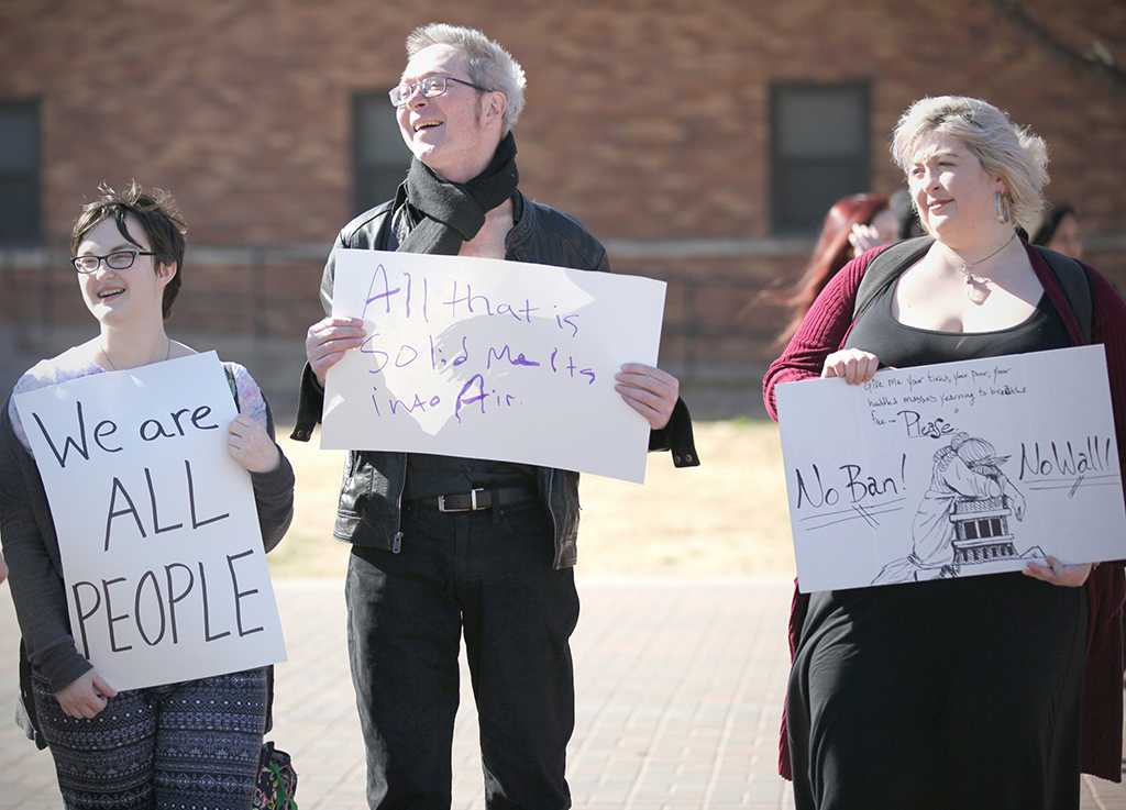 Catherine Stepniak, psychology and sociology sophomore, Brinton Coxe, assistant professor of humanities, and Emily Schackleford, marketing senior, hold up their signs at the rally against the immigration executive order, on Feb. 1st. Photo by Bridget Reilly